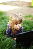 Little girl with a laptop lying on the grass — Stockfoto