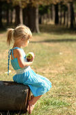 Beautiful little girl with apple on nature — Stock Photo