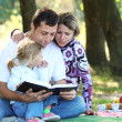 Young family read the Bible in nature - Foto Stock