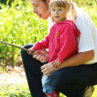 Father with a small daughter at the lake in rubber boots — Stock Photo