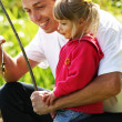 Father with a small daughter at the lake in rubber boots — Stockfoto