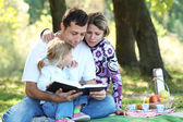 Young family read the Bible in nature — Stock Photo