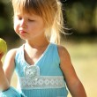 A beautiful little girl eating an apple outdoors — Stock Photo