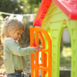 Little girl with a children's playhouse — Stock Photo #19053599