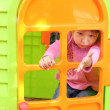 L little girl with children's playhouse — Stock Photo #19053603