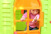 L little girl with a children's playhouse — Stock Photo