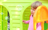 Little girl with a children's playhouse — Stock Photo