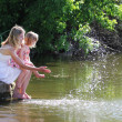 Mother and her little daughter squirting water at the lake — Stock Photo