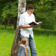 Father with baby daughter reading the Bible - Stock Photo