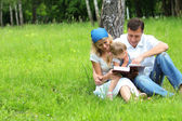 Family with a young daughter reads the Bible — Stock Photo