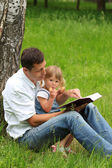 Father with baby daughter reading the Bible — Stock Photo