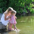 Mother and her little daughter squirt water at the lake — Stock Photo