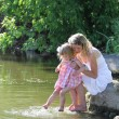 Girl and her little daughter squirting water at the lake — Stock Photo