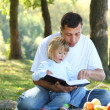 Father with young daughter read Bible in nature — Stock Photo #22218293