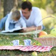 Young father with baby daughter reading the Bible on a picnic - Stock Photo