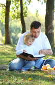 Father with a young daughter read the Bible in nature — Stock Photo