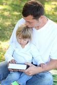 Padre con una joven hija lea la biblia en la naturaleza — Foto de Stock