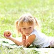 Beautiful little girl outdoors with apple — Stock Photo