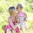 Mother and her little daughter on the grass outdoors — Stock Photo