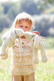 Beautiful little girl in nature with rabbits — Stock Photo
