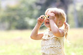 Beautiful young girl on nature with binoculars, — Stock Photo