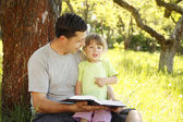 Father with his little daughter reads the Bible — Stock Photo