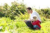 Dad and little daughter near a lake — Stock Photo