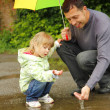 Girl with an umbrella in the rain with his father — Stock Photo