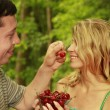 A couple in love at a picnic with cherries — Stock Photo