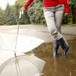A man with an umbrella in his boots and puddle — Stock Photo