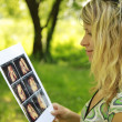Pregnant girl on nature with ultrasound photos — Stock Photo