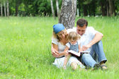 Young family reading the Bible — Stok fotoğraf