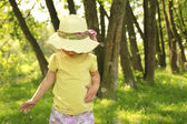 Beautiful little girl in a hat on the nature — Stock Photo