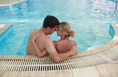 Loving couple in the water pool — Stockfoto