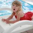 Girl in water pool on sun lounger — Stock Photo #28468331