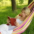 Stock Photo: Young girl reading a book while lying on a hammock
