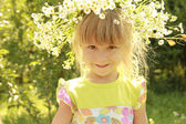 Beautiful little girl in a wreath of flowers on the nature — Stock Photo