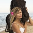 Stock Photo: Girl with a horse by the sea