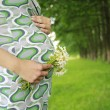 Belly of a pregnant woman on the nature — Stock Photo