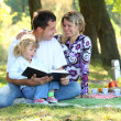Young family reading the Bible in nature — Stock Photo
