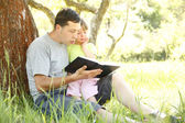 Young father with his little daughter reads the Bible — Stock Photo