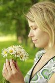 Chica joven con un ramo de flores en la naturaleza cerca de la paja — Foto de Stock