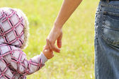 Parent holds the hand of a small child — Stock Photo