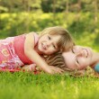 Young mother and her little daughter playing on grass — Stock Photo #31969417