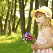 Stock Photo: Beautiful little girl with bouquet of flowers in nature