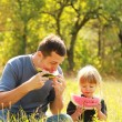 Stock Photo: Beautiful little girl with her father eats watermelon in nature