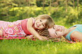Young mother and her little daughter playing on grass — Stock Photo
