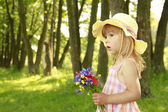 Beautiful little girl with a bouquet of flowers in nature — Stock Photo