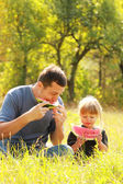 Beautiful little girl with her father eats watermelon in nature — Stock Photo