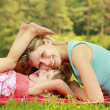 Mother playing with her little daughter on the grass — Stock Photo